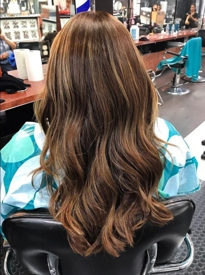 Brunette woman in a salon chair with long wavy permed hair