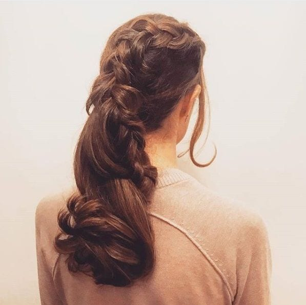back view of a brunette with her hair in a curly wedding ponytail with a braided detail