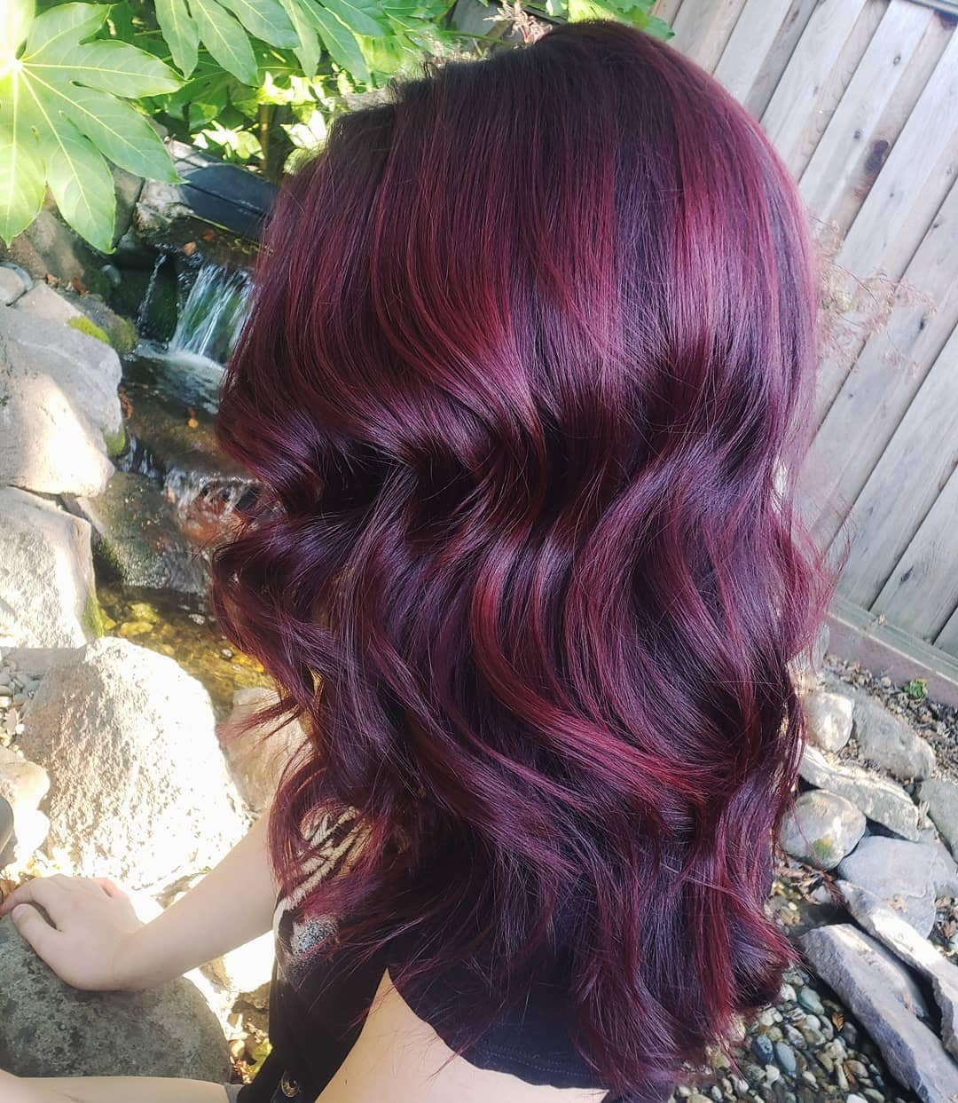 Woman with mid-length curly burgundy mahogany hair