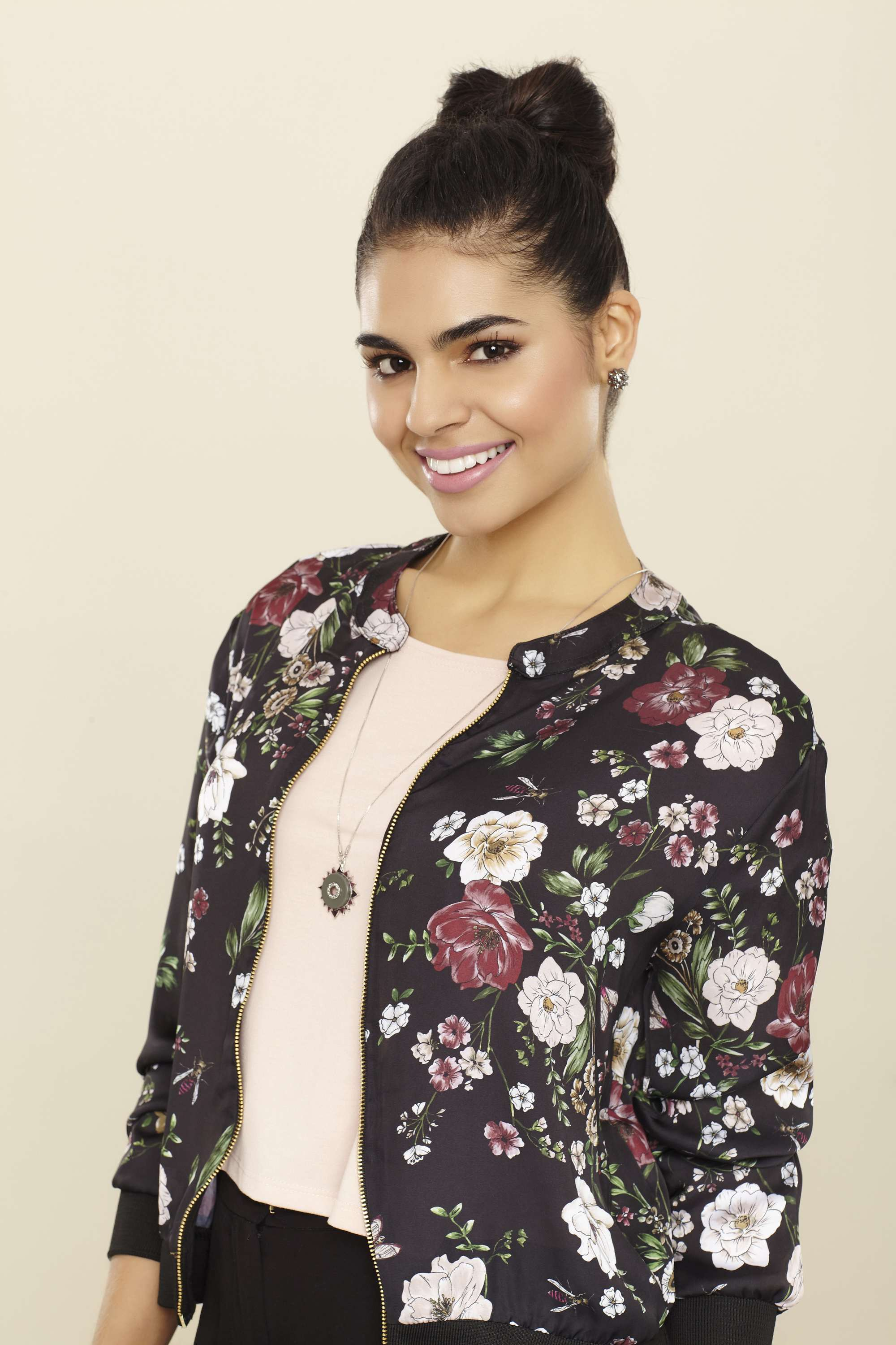 woman with dark brown hair with centre braid in high bun wearing a floral jacket