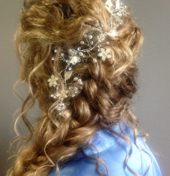 blonde curly hair in french braid swept over one shoulder with floral accessories