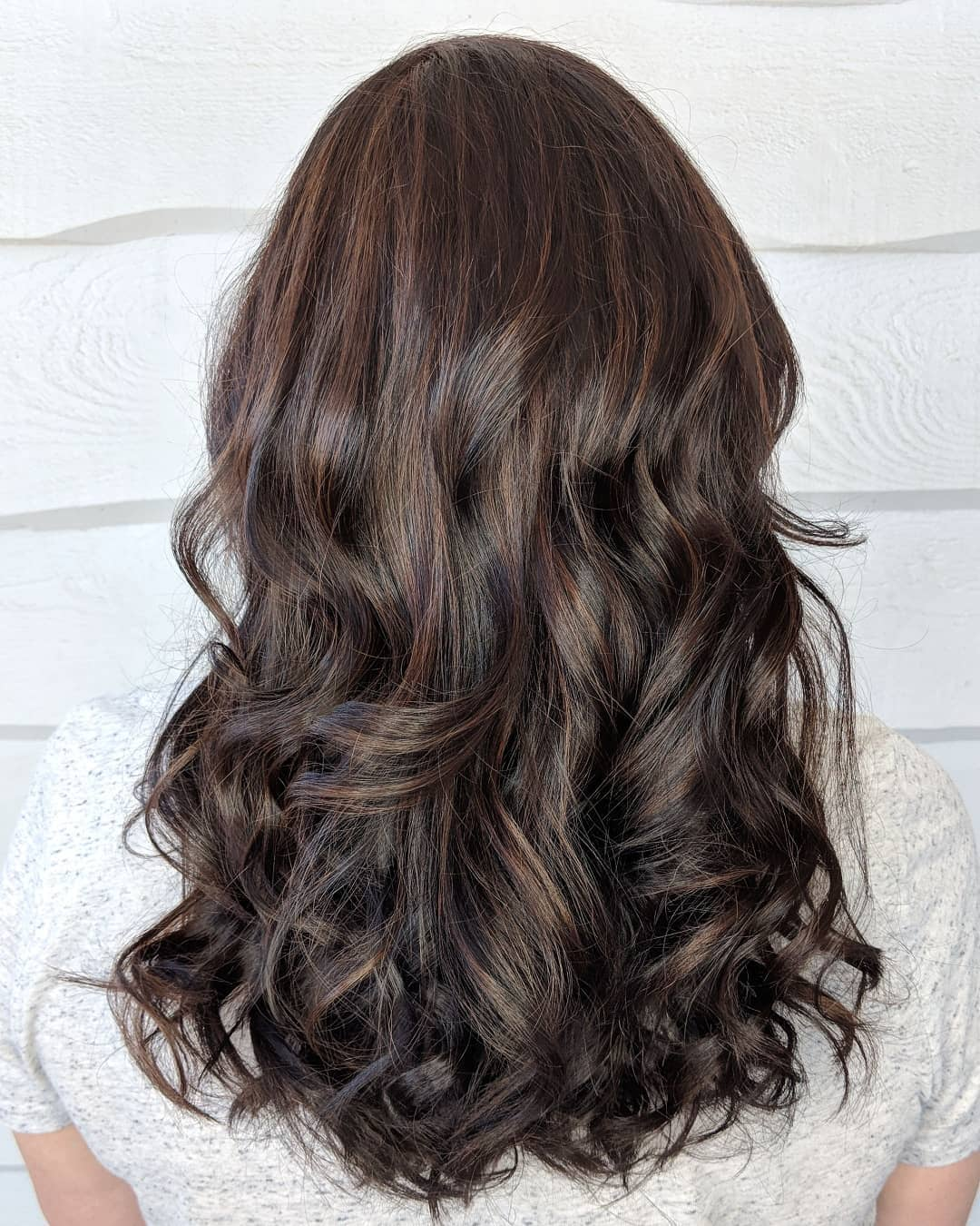 Woman with medium length curly brunette hair with mahogany highlights