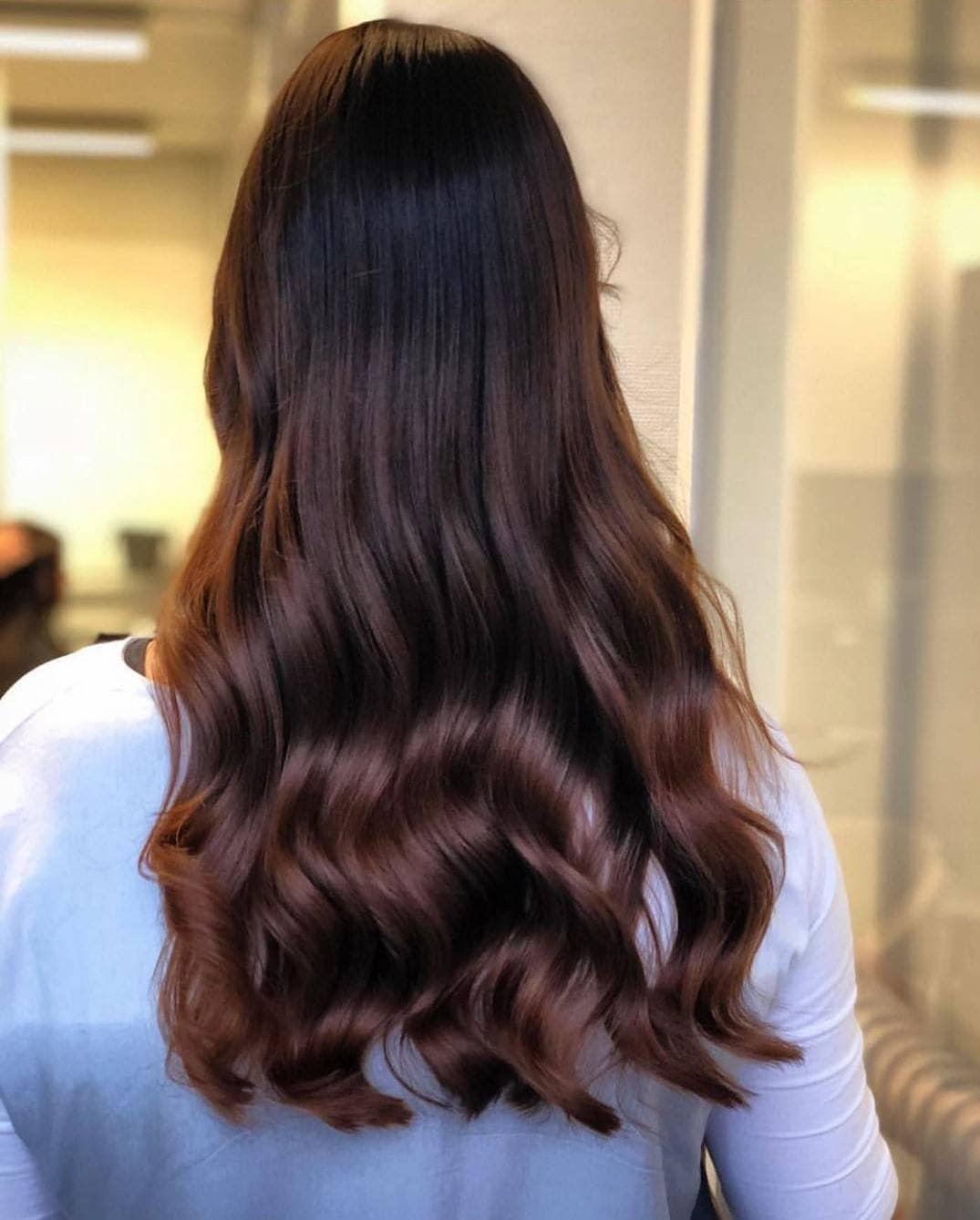 Woman with long glossy mahogany waves
