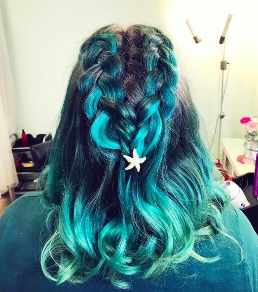 back view of a woman with blue and green hair and double dutch braid style
