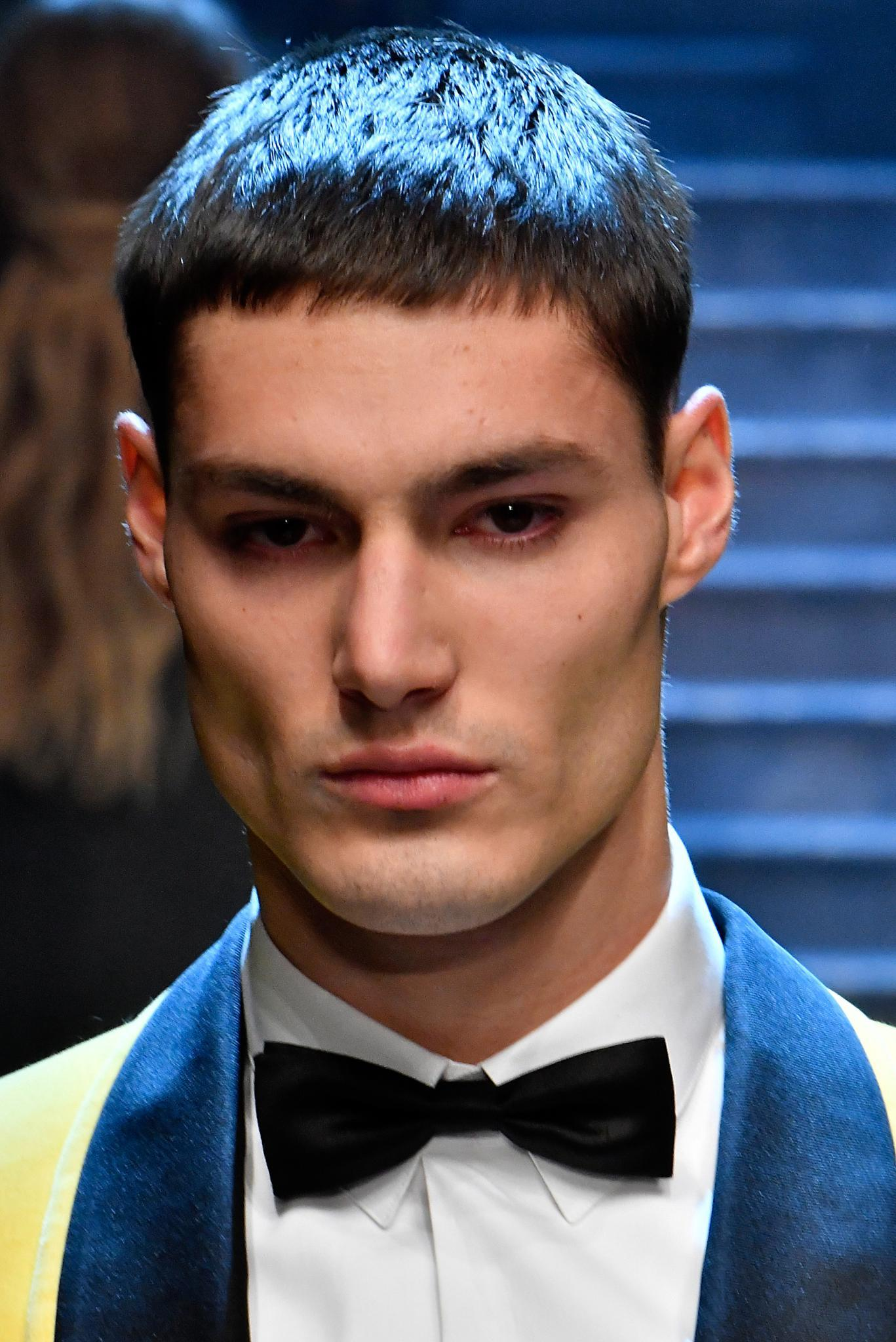 Crop haircut: Close-up of a brown haired model with a French crop haircut, wearing a tux