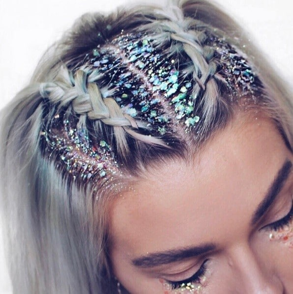 blonde woman with her hair in braids with glitter roots