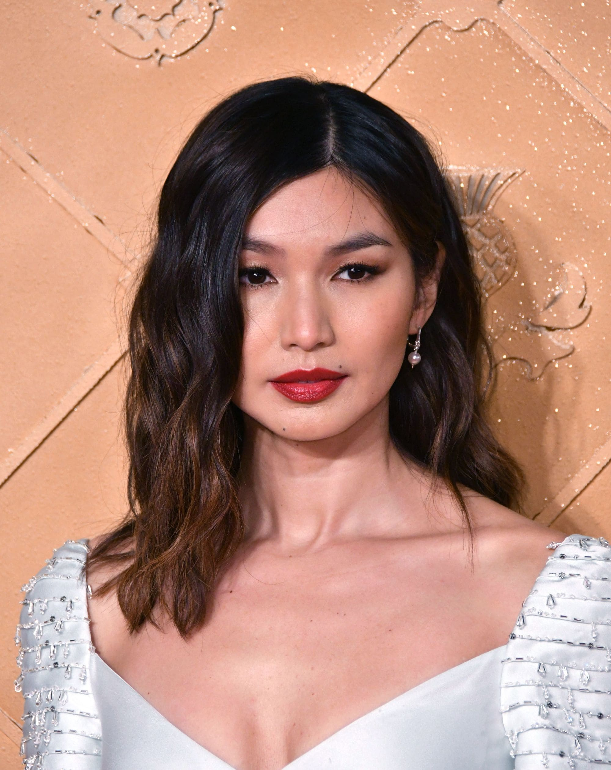 Shoulder length layered hair: Gemma Chan with shoulder length wavy layered dark hair