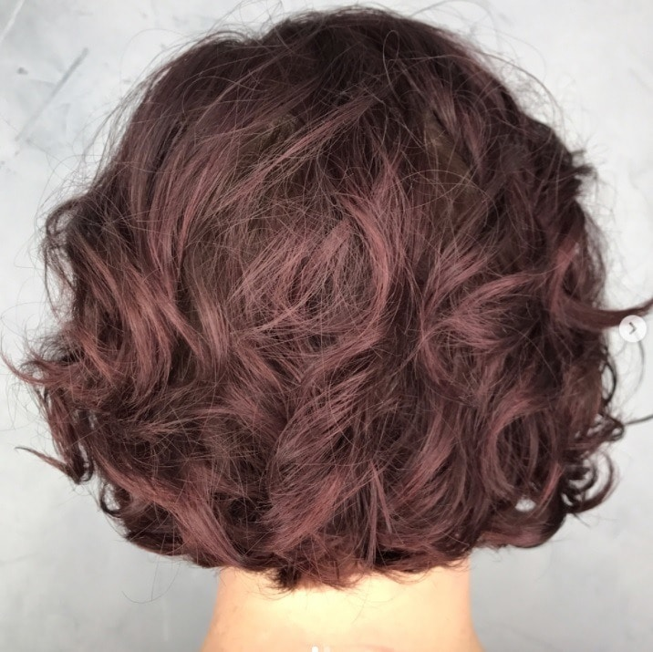 backshot of woman with graduated bob with loose perm hairstyle at salon