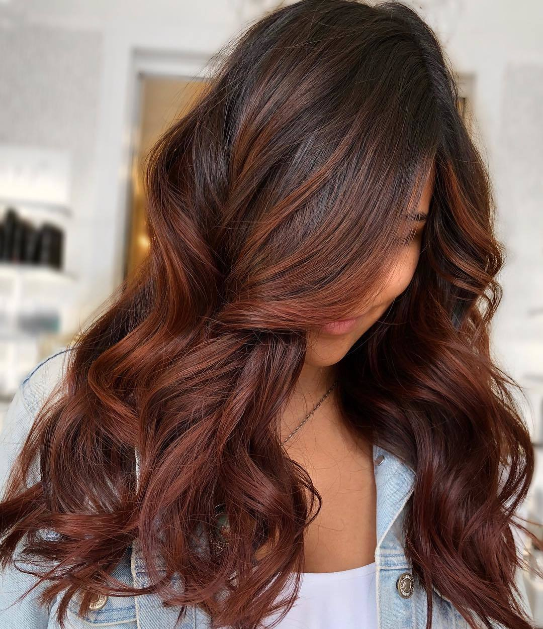 Woman with brown hair with reddish chestnut hair highlights