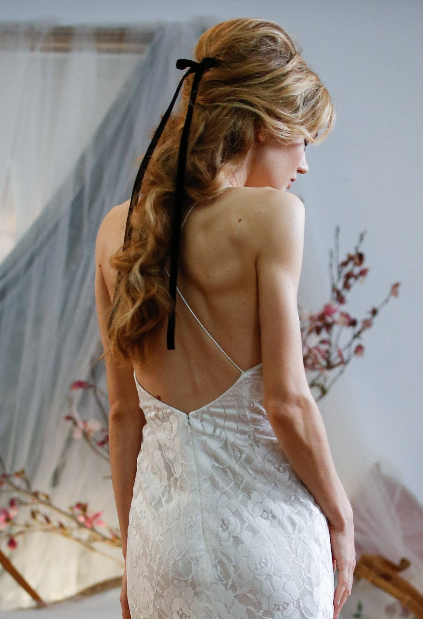 bridal model with her blonde hair in a half up half down hairstyle with a black ribbon accessory