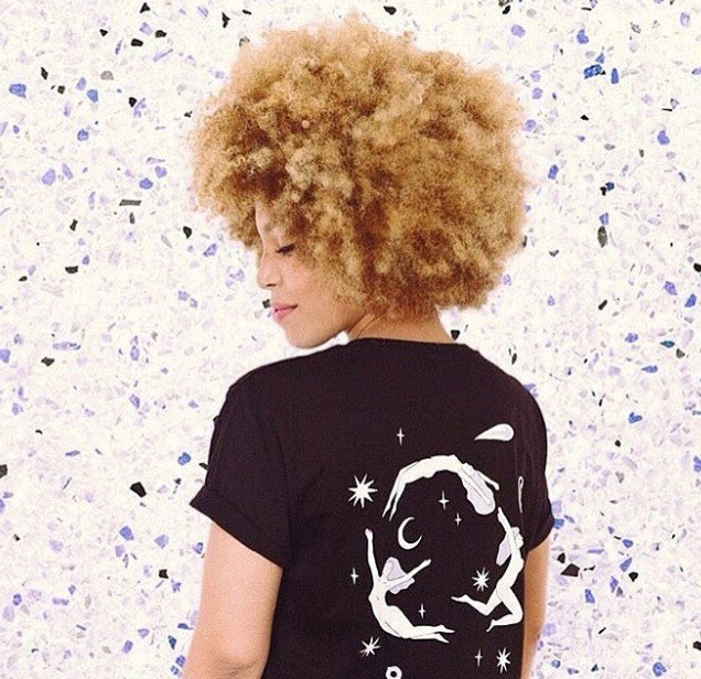 backshot of woman with golden blonde afro hair, wearing black outfit