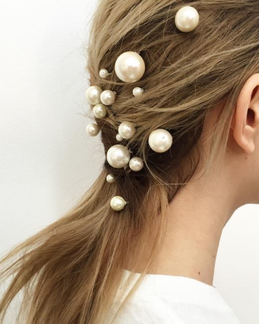 blonde model with twisted low ponytail with pearl accessories placed in hair from back side view