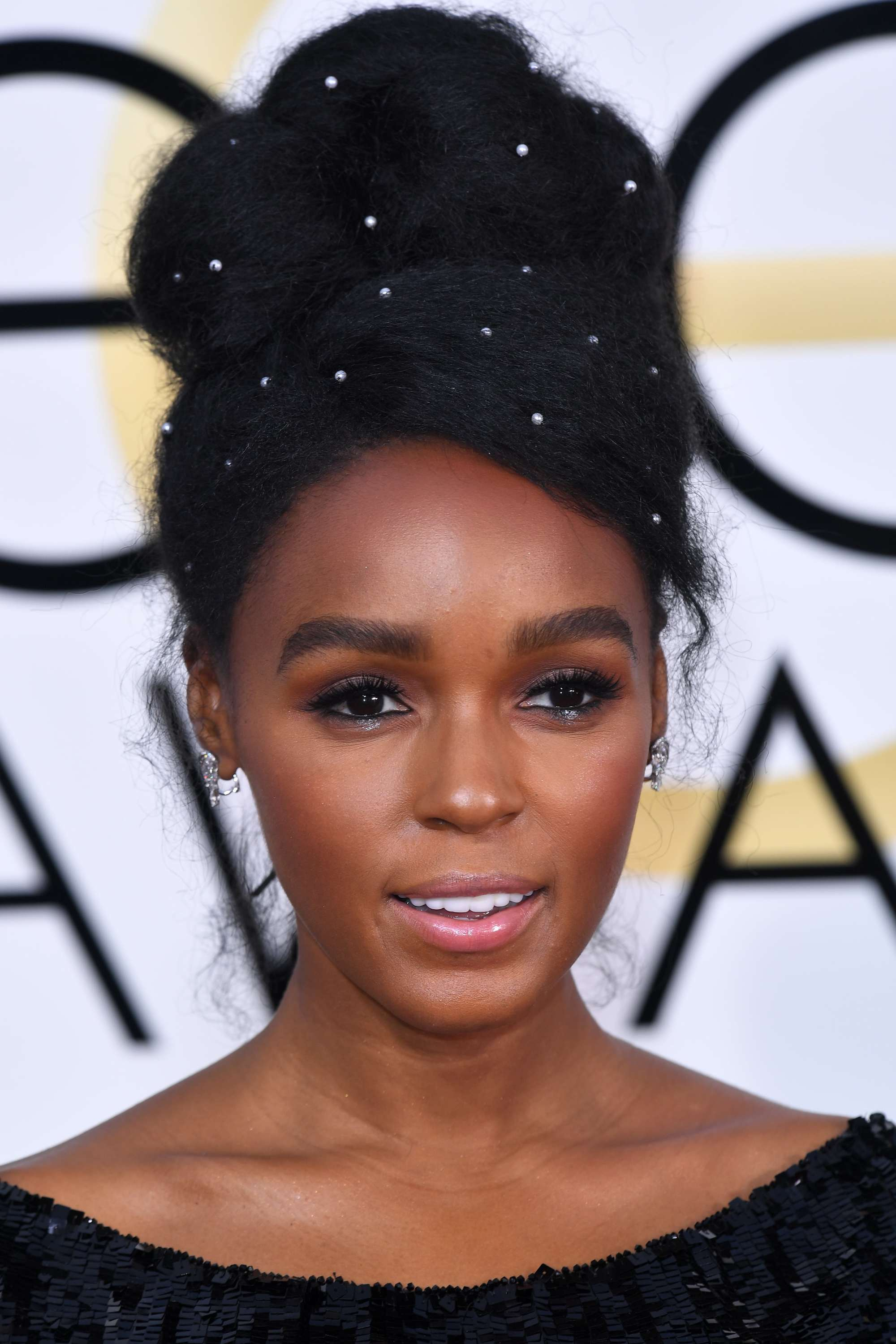 black prom hairstyles: janelle monae with a high bun updo with pearl hair accessories at the met gala