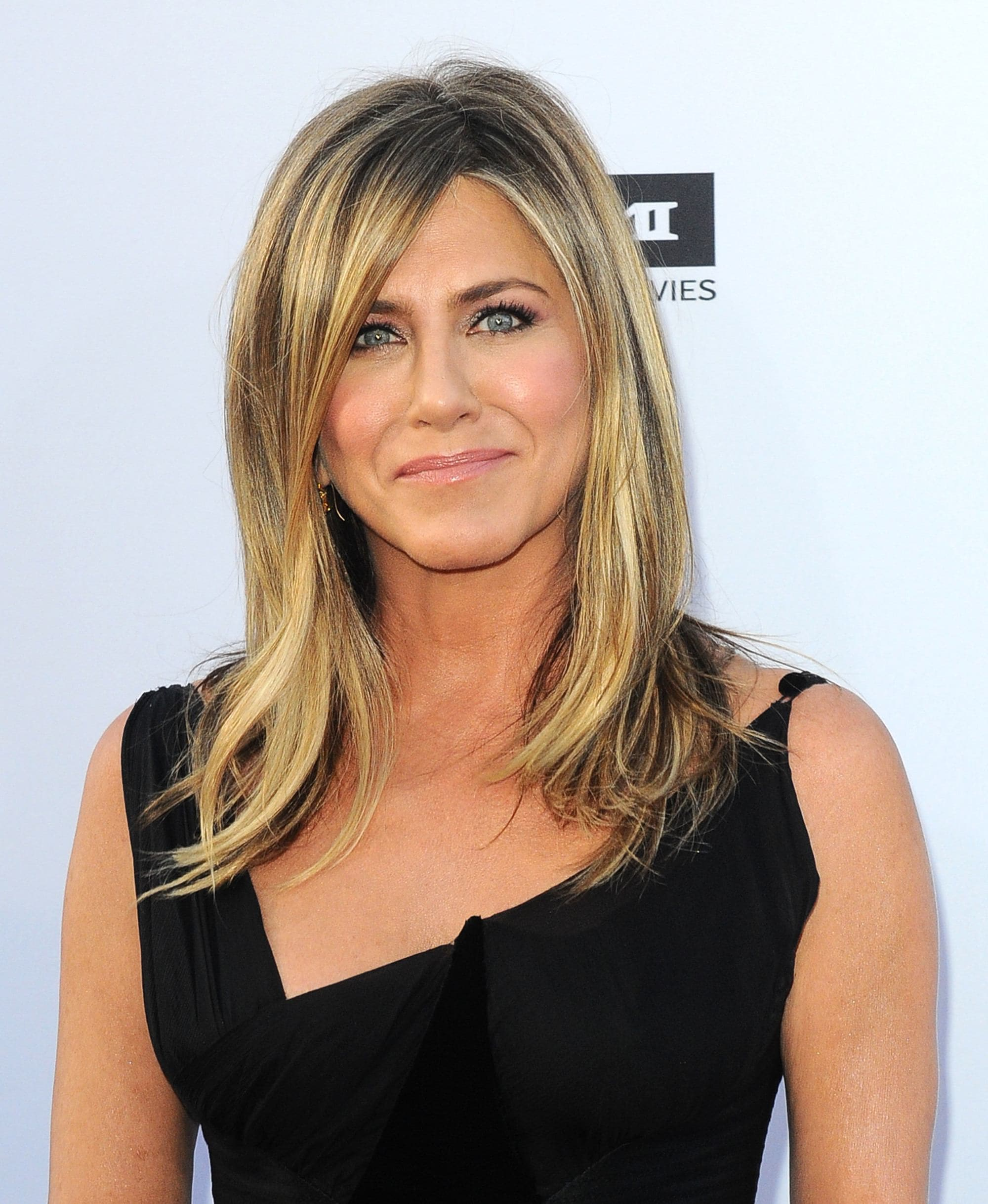 Shoulder length layered hair: Jennifer Aniston with mid-length blonde hair with a side fringe and layers