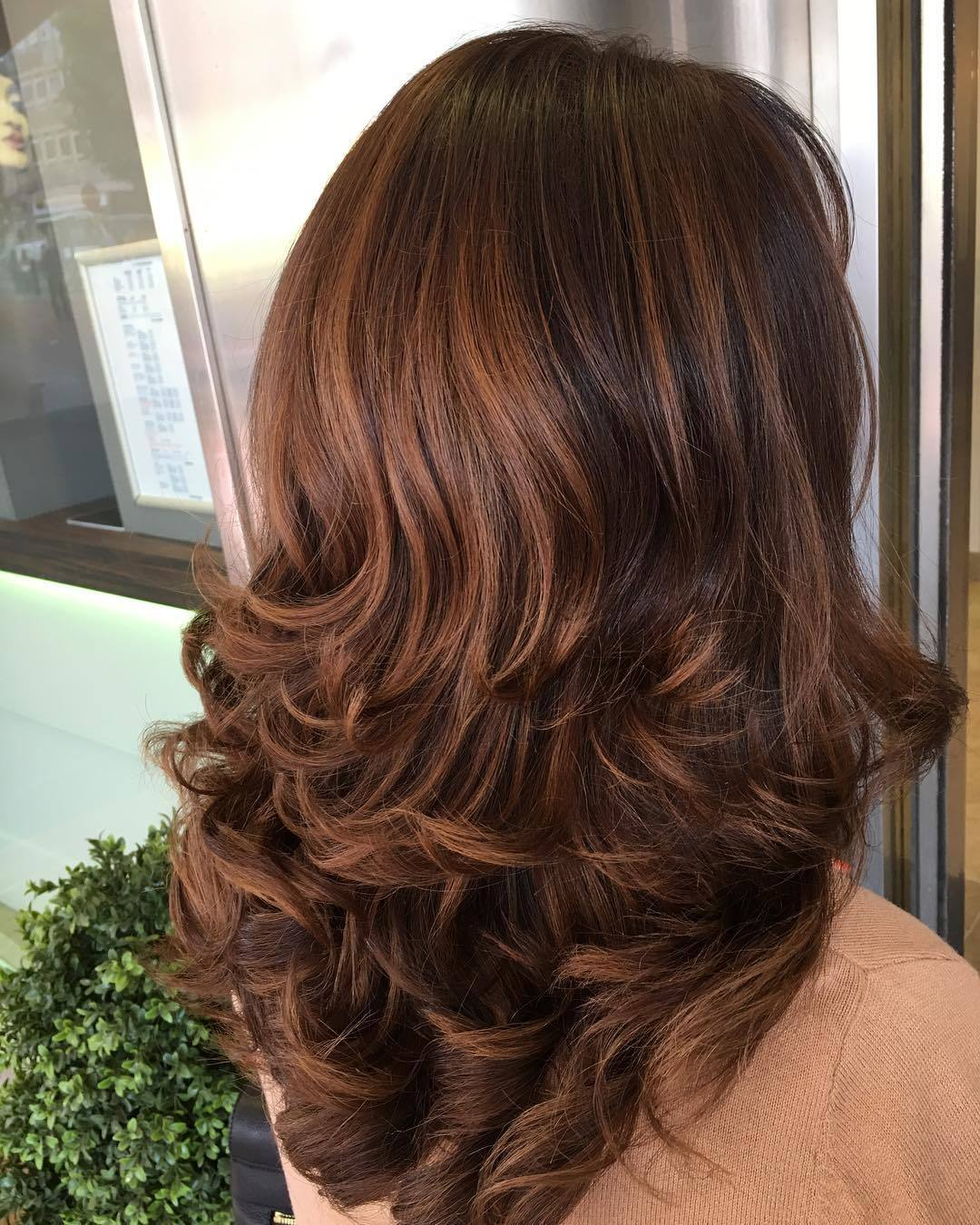 Woman chestnut brown hair styled into a blow out