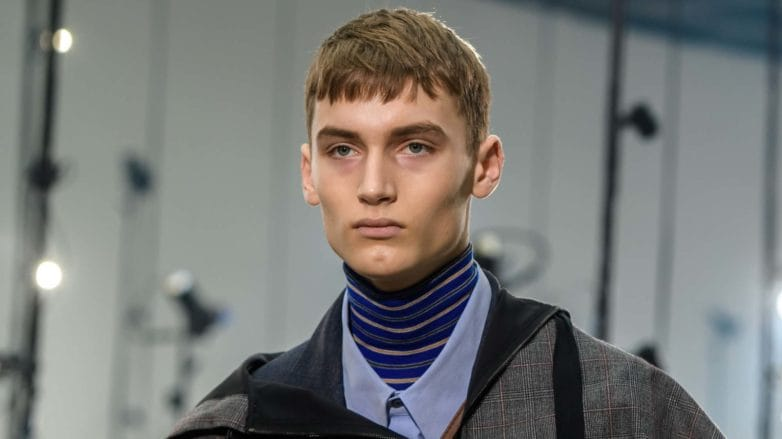 Crop haircut: Runway shot of a model with a light brown French crop haircut, wearing a striped high neck, a blue shirt and a grey layered jacket