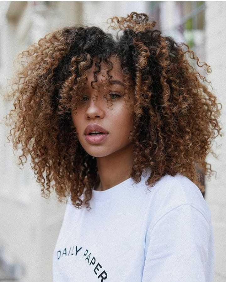Woman with light chestnut brown curly hair with bangs