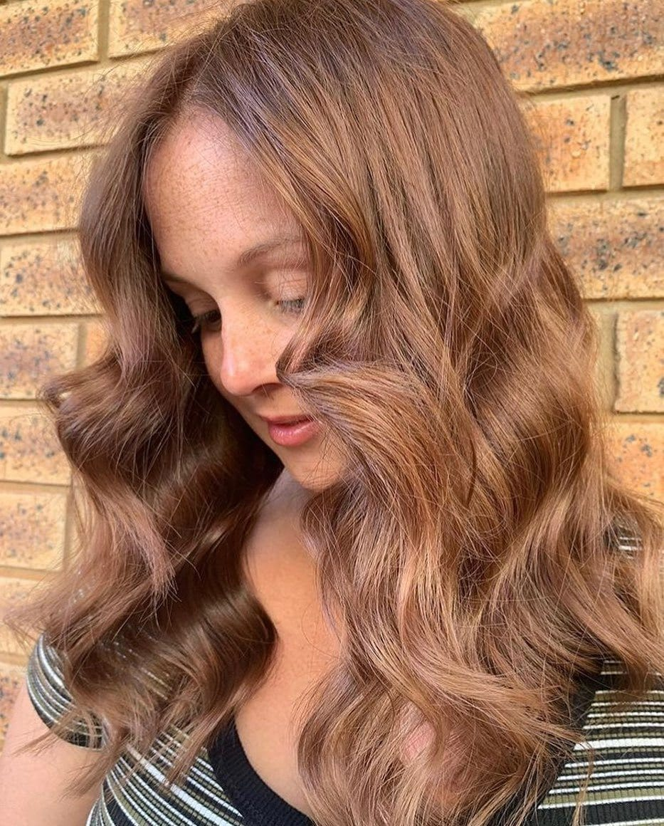 Woman with caramel and chestnut brown hair styled into waves