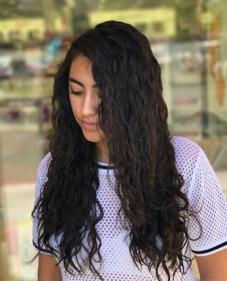 Woman with long dark brown wavy permed hair wearing a lilac tshirt