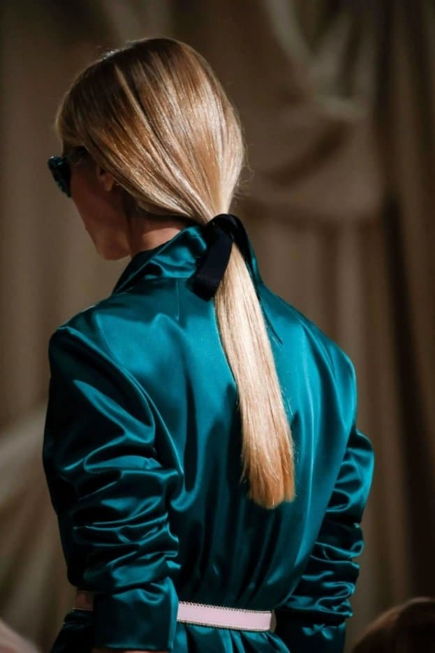 blonde model on the runway with her hair in a low ponytail with a black ribbon hair accessory