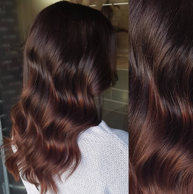 woman with medium length brunette hair with mahogany balayage highlights
