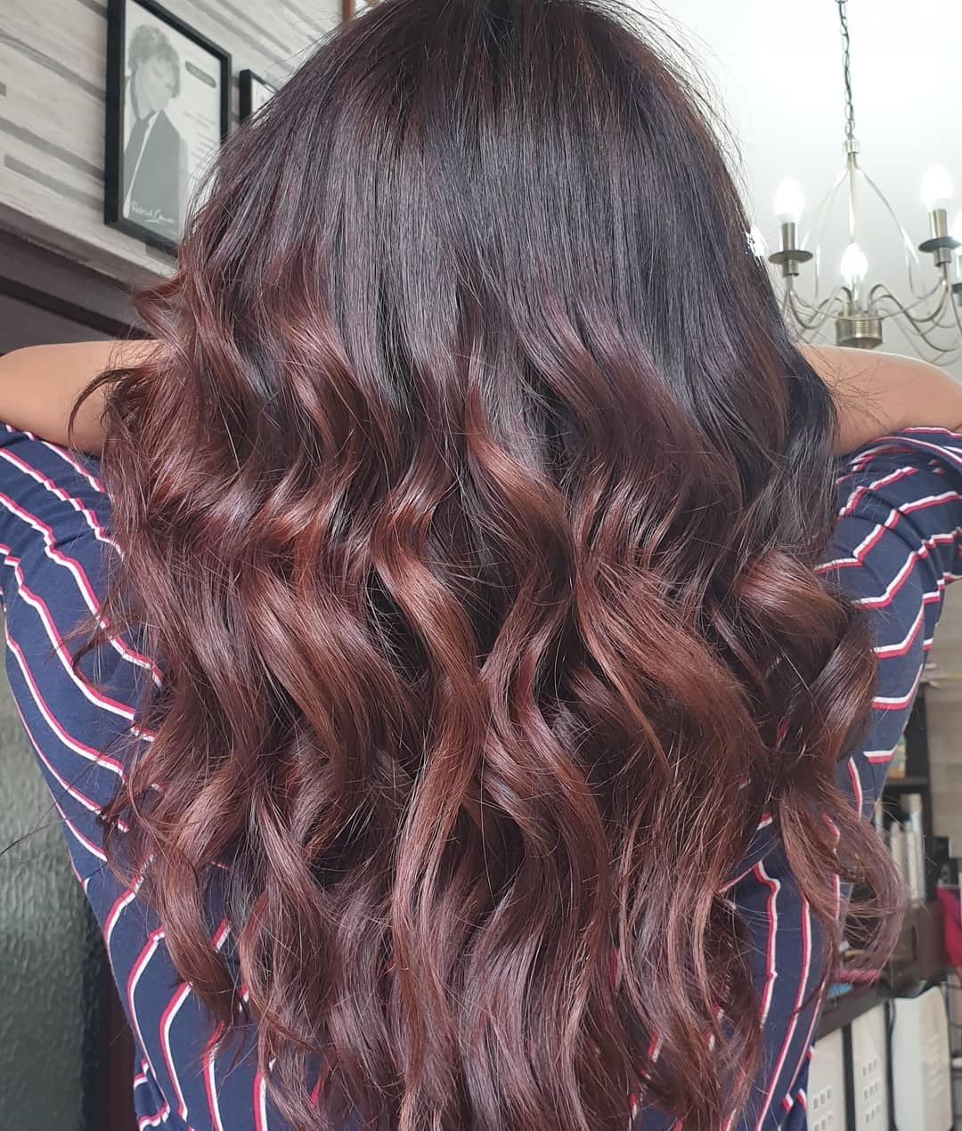 Woman with curly dark brunette hair with mahogany highlights