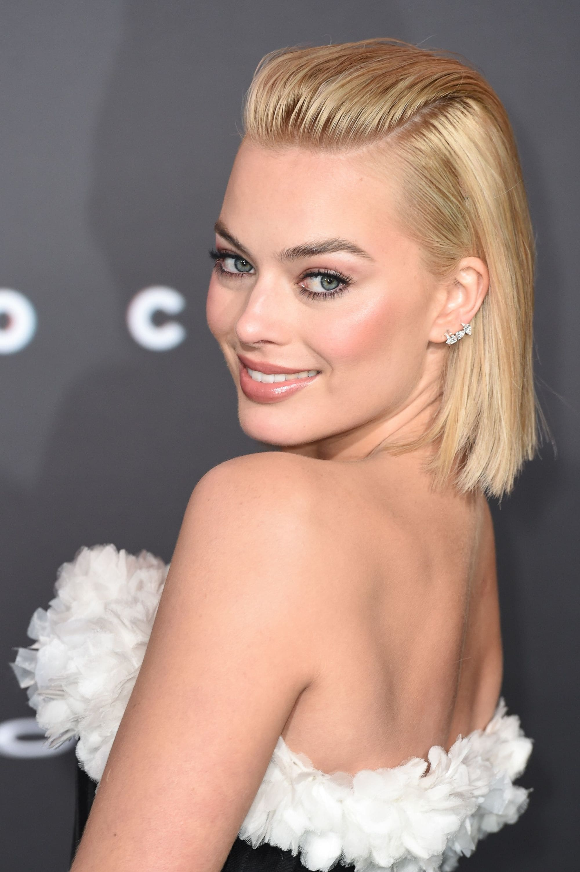 australian actress margot robbie with her shoulder length blonde hair in a slicked back quiff hairstyle