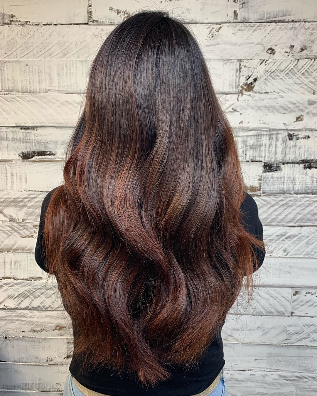 Woman with long chestnut brown hair with subtle highlights