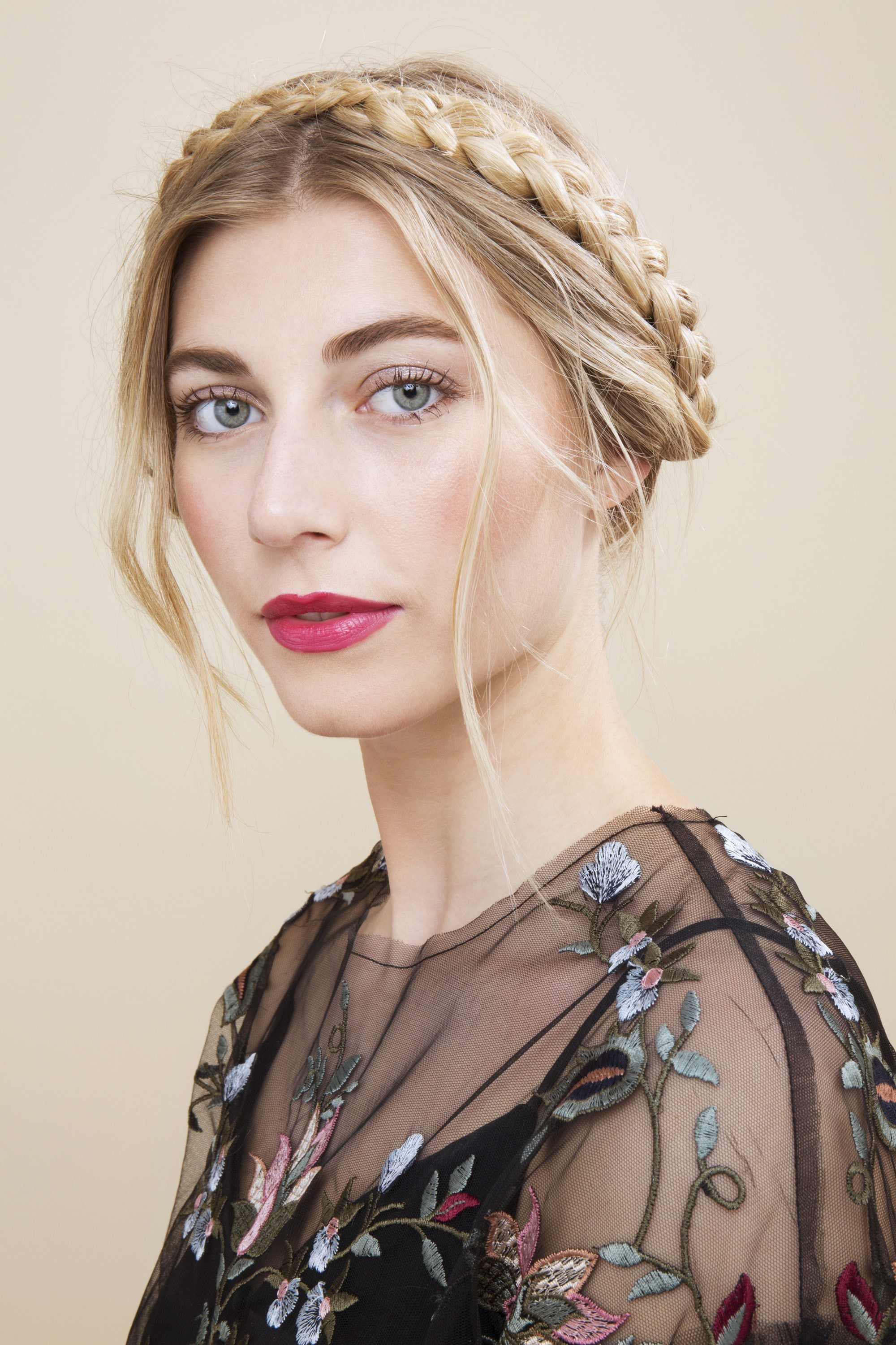 blonde model wearing a blackfloral mesh top with her hair in a milkmaid braid updo with loose face-framing pieces of hair