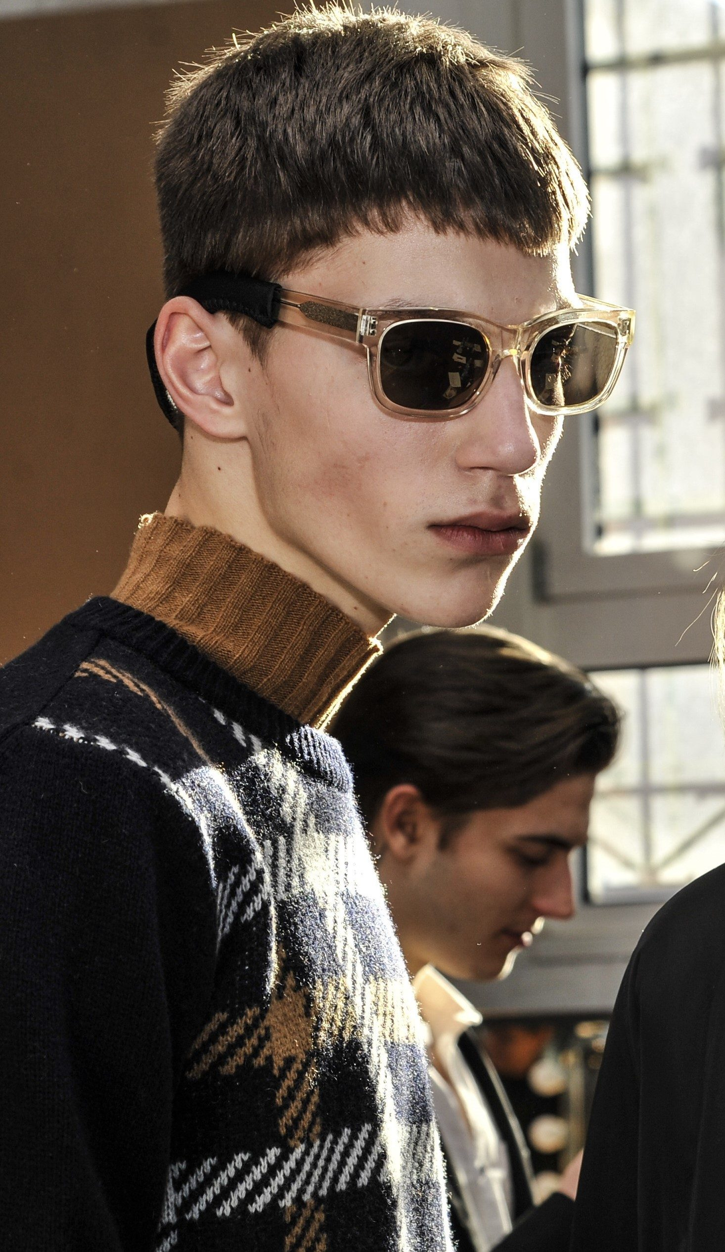 Crop haircut: Brunette male model backstage wearing sunglasses with a french crop haircut