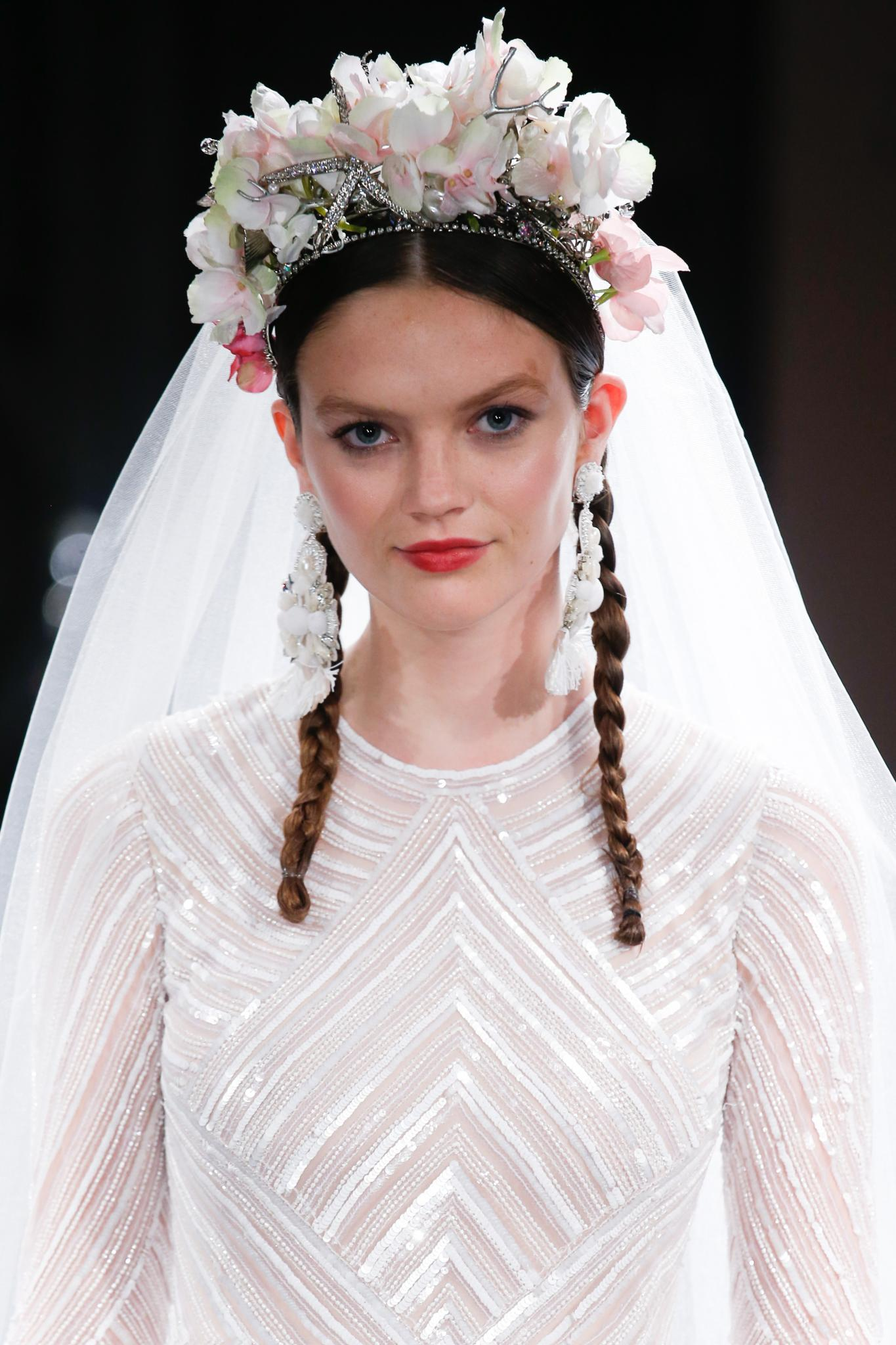 runway model with dark brown hair with braided pigtails under large flower crown and veil