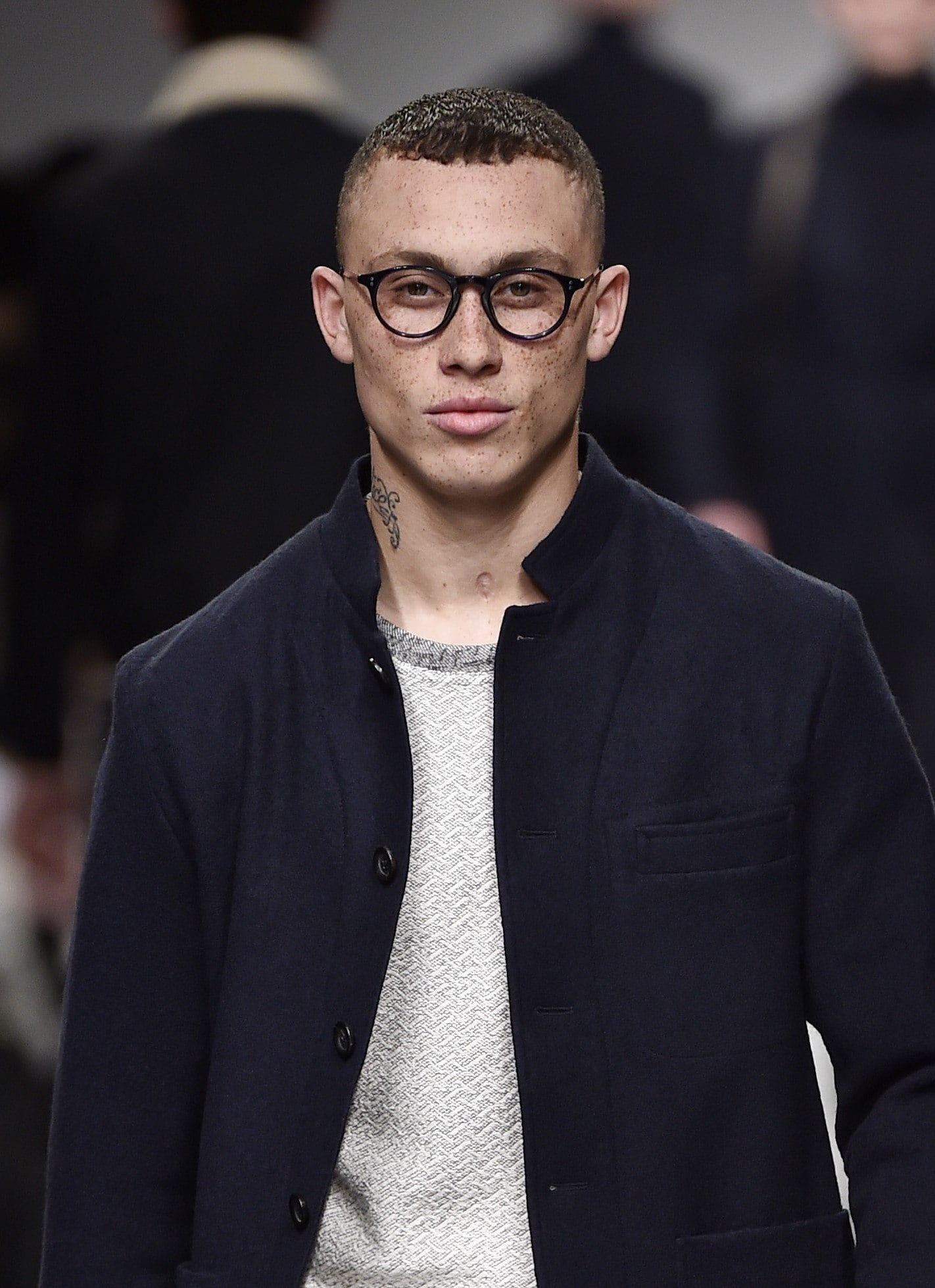 Crop haircut: Runway shot of a male model with a short crop haircut, wearing a navy jacket and glasses