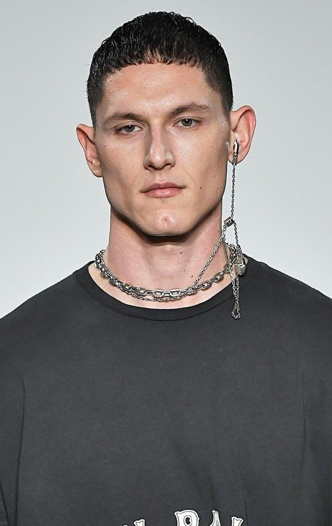 Crop haircut: Brown haired male model with a short, gelled French crop, wearing a grey t-shirt and a chain necklace