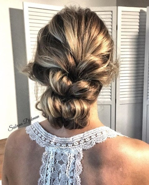 back view of a blonde woman with her hair in a pull through braid updo