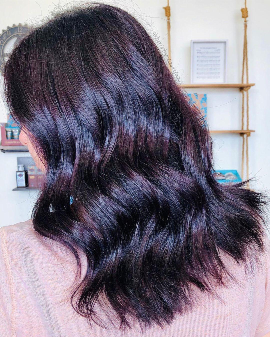 Woman with purple toned mahogany medium length wavy hair