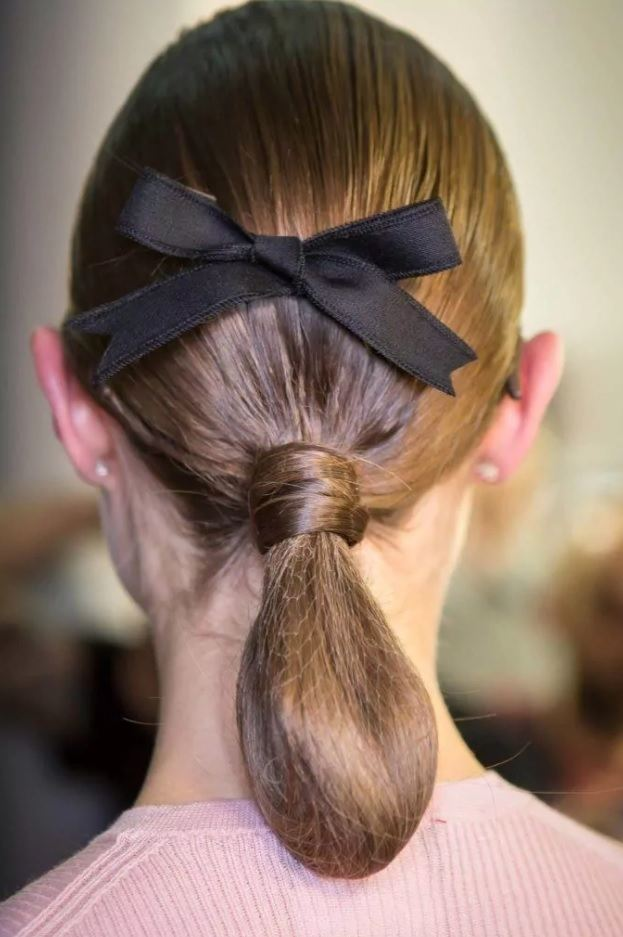 brunette model with a low chignon hairstyle with a black bow accessory