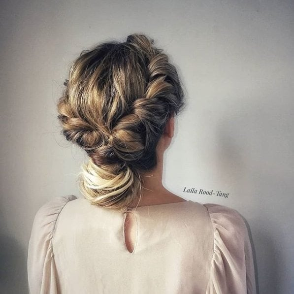 back view of a blonde woman with her hair in a twisted detail updo with a bun