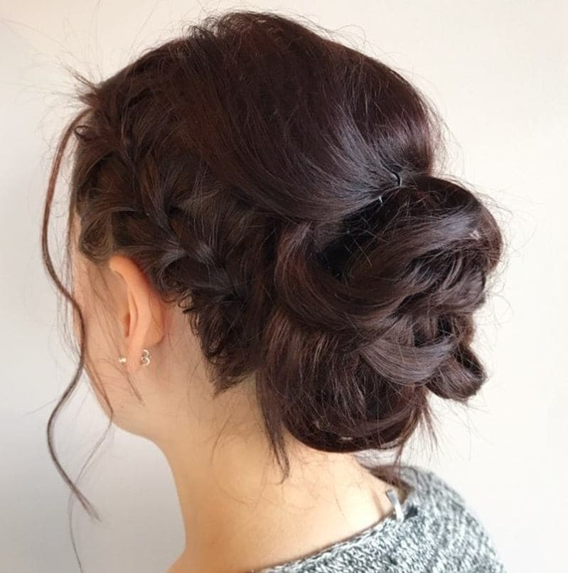 woman with her dark brunette mahogany hair in a braided bun updo