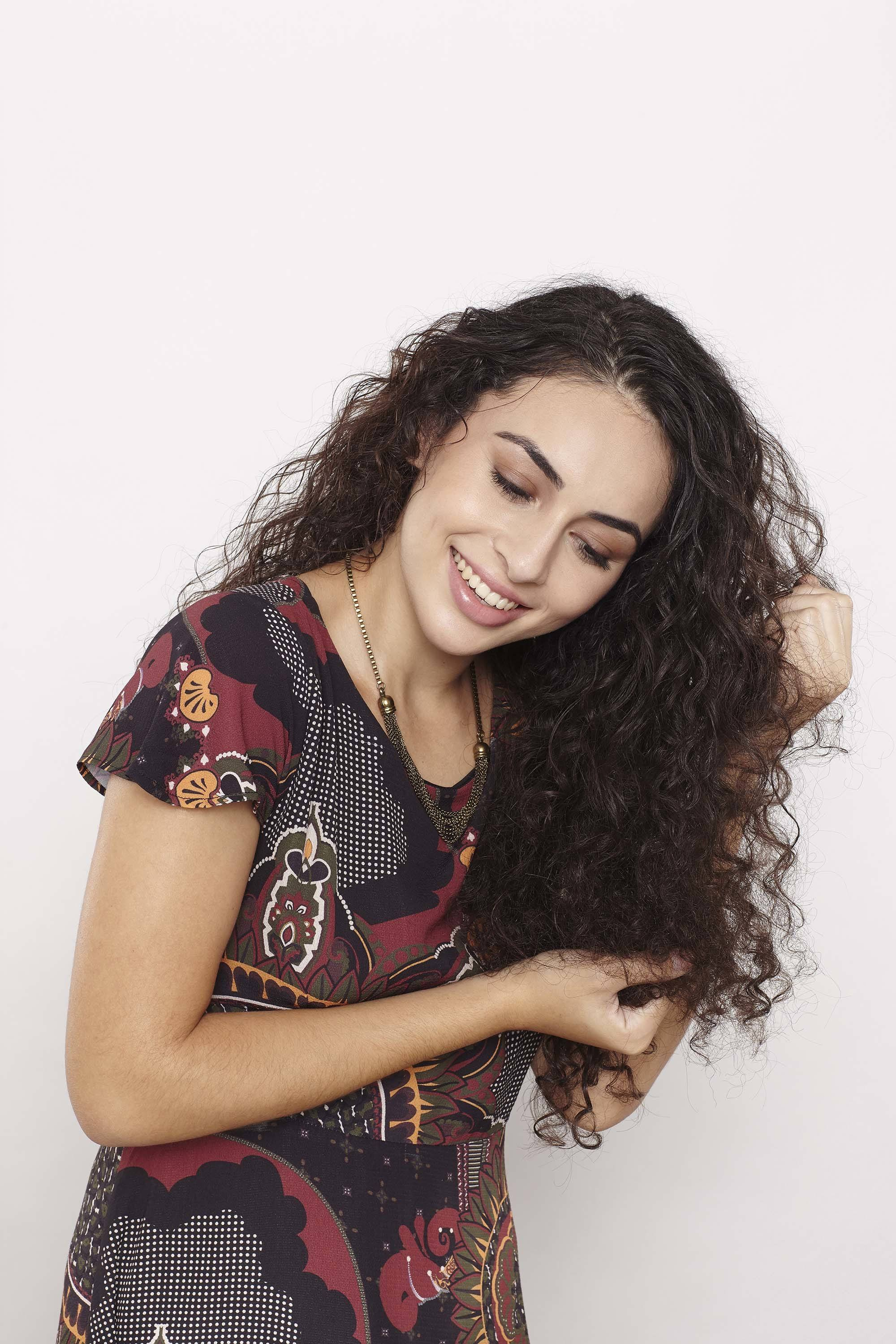 Model wtih long curly brown hair scrunching in hair product to the lengths wearing pattern top