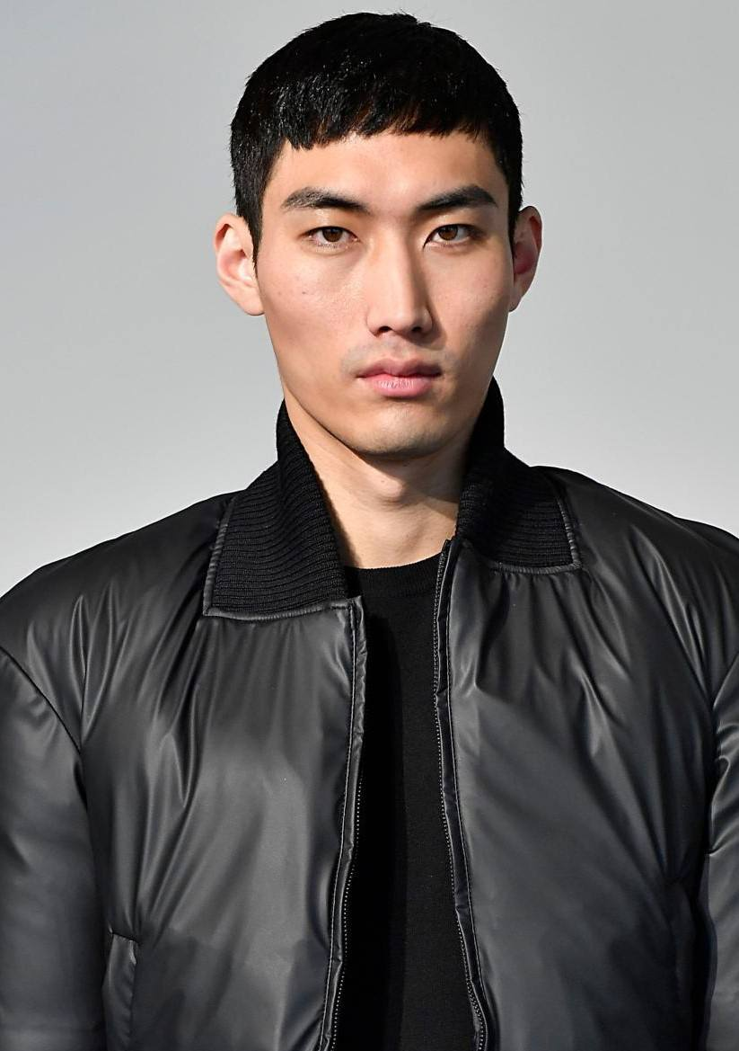 Crop haircut: Close-up of an Asian male model with dark brown hair in a French crop style, wearing a black bomber jacket