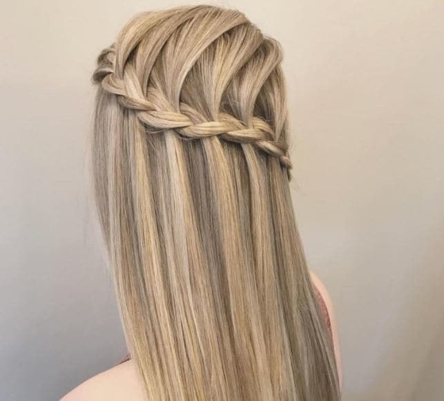 behind view of a woman with straight blonde hair styled in a waterfall braid