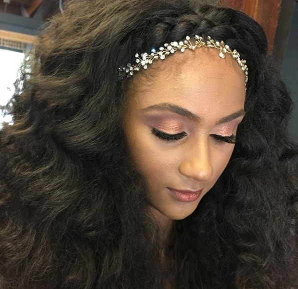 close up of a brunette with voluminous wavy hair with a braided fringe with a floral headband accessory
