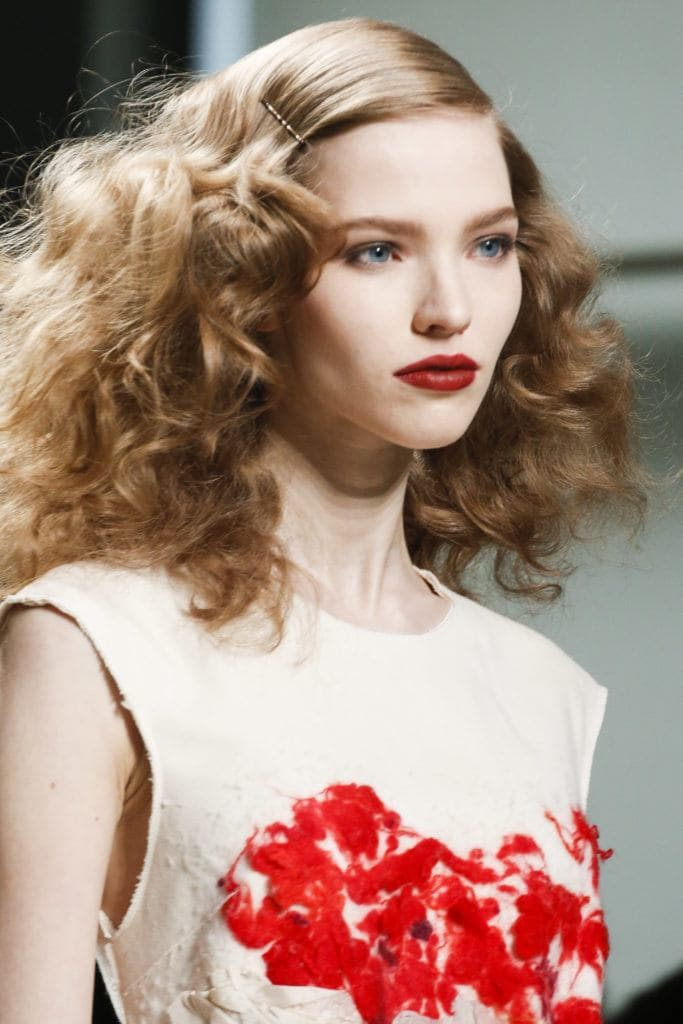 runway shot of a brunette model with 1920s screen siren curly frizzy hair