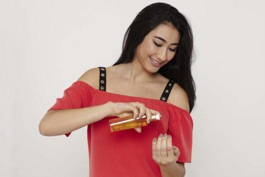 woman with long dark brown hair applying a hair oil