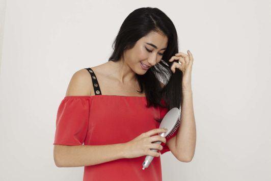 woman with long dark brunette hair using a hair brush