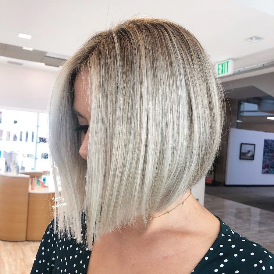 Woman with silver blonde hair and sharp angled bob hairstyle in a salon