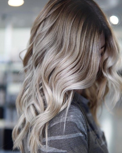 Ash blonde ombre: Close-up of a woman with wavy ash blonde hair with grey shadow roots