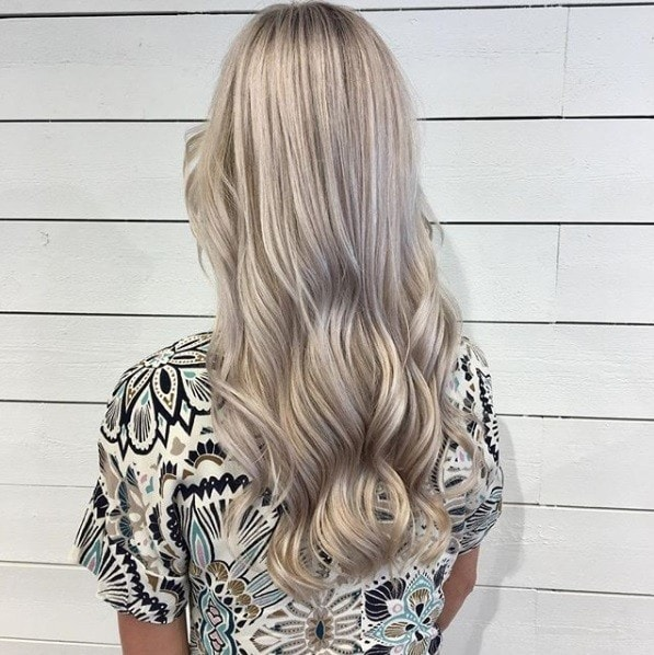 Ash blonde ombre: Back view of a woman with long creamy blonde waves, wearing a patterned top