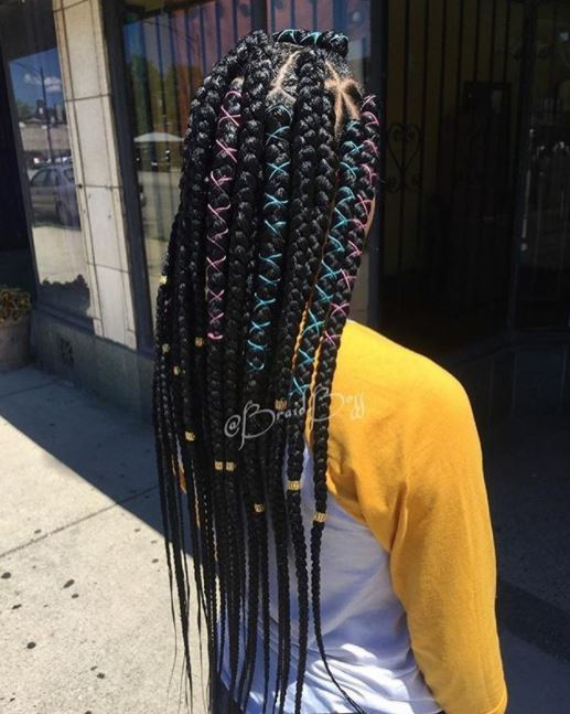 back view of girl with long black box braids that are chunky at the top and slim at the bottom