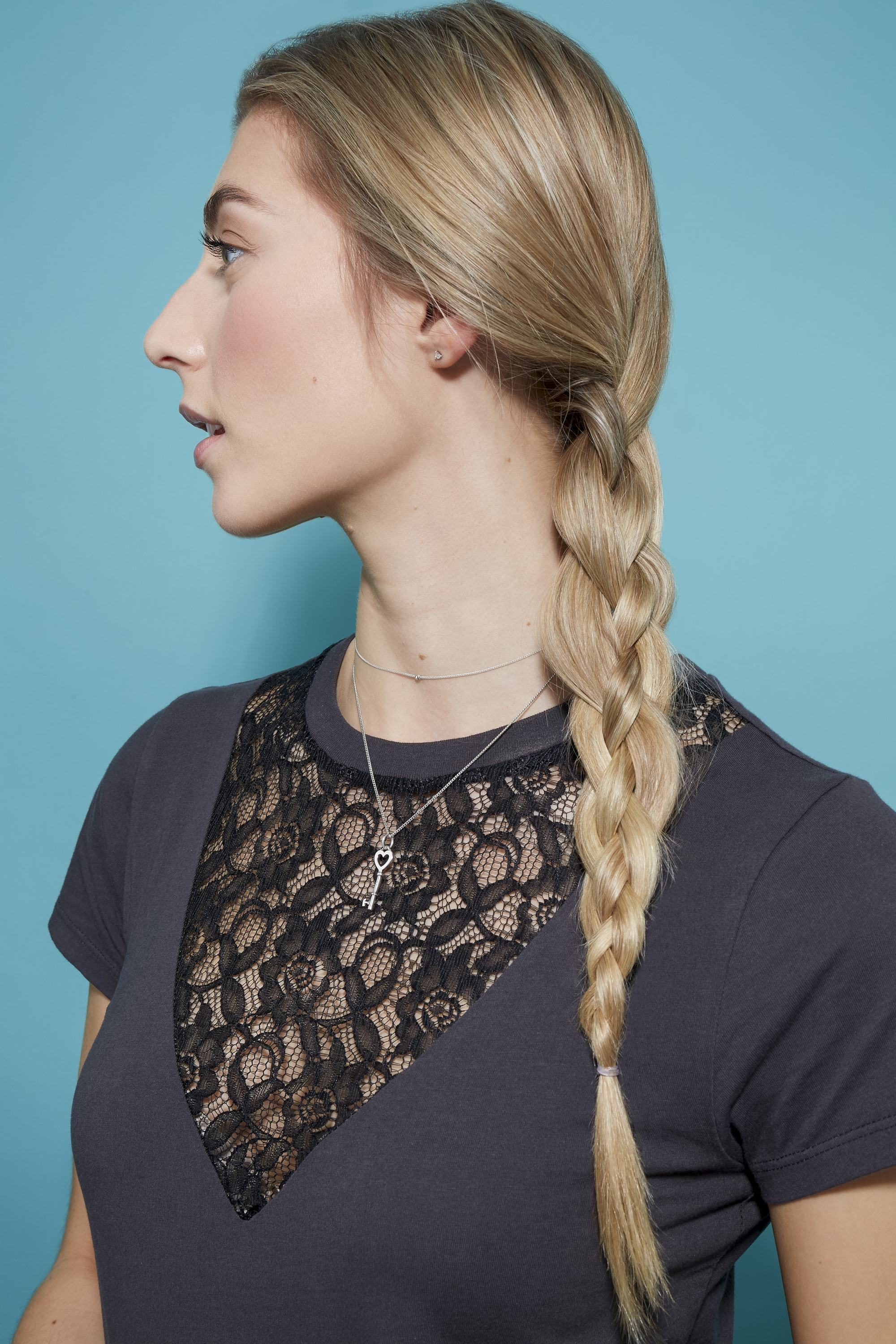 Braids for long hair: Woman with long blonde straight hair in side braid wearing a black top